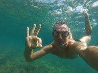 man swims under water