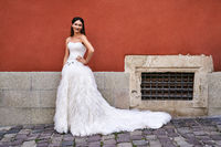 Beautiful bride wearing gorgeous elegant stylish white floor length dress in old beautiful European city on a wedding day.