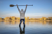 silhouette of a male stand up paddler in fall scenery