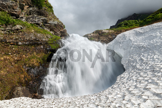 Summer landscape - mountain waterfall falling into the snowfield