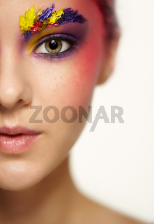 Unusual female face art make-up with paint on brows and around eyes.