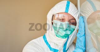 Arzt in Schutzkleidung mit geschlossenen Augen wegen Erschöpfung bei Coronavirus Pandemie