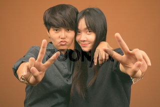 Young Asian lesbian couple together and in love against brown background