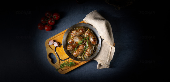 Homemade white sausage fried with onion and herbs