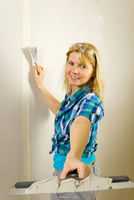 Woman putty plaster. Builder female indoor worker plastering wall with spatula trowel tool.