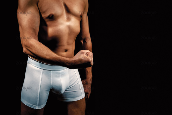 man in white briefs with a fist