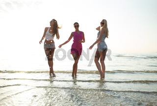 happy female friends dancing on beach