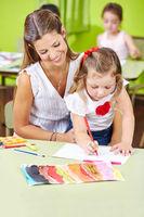 Tagesmutter malt mit Kindern