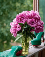 Beautiful unopened red purple peony in vase, green shoes near. Close up view of red purple piones on greeny background. Copy space for text. Vertical. Authentic shot. Cottagecore, fresh air, slow life concept