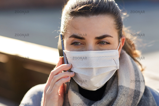woman in face mask calling on smartphone in city