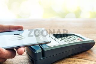 person holding phone against POS payment terminal
