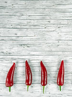 Design of light wood background with chili peppers