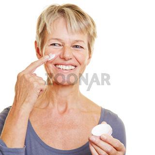 Alte Frau pflegt Haut mit Gesichtscreme