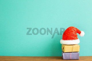 Christmas concept. Stack of gift boxes with santa claus hat on wooden table with green background