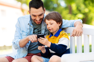 father and son with smartphone at park