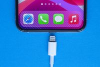 Calgary, Alberta, Canada. Nov. 19, 2020. An iPhone Pro with a Lightning to USB Cable on a blue background.