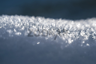 Selective focus on sunlit snow heap with snowflake crystals with blue winter background