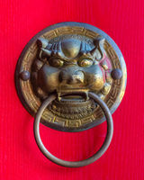 Dragon head door handle on the red door in a buddhist temple in the Sanya Nanshan Cultural Center