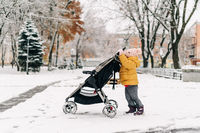 Toddler child pushing stroller with sibling in it. Winter snowy day. Christmas time