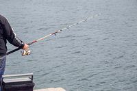 Fisherman standing on edge of dock with fishing rod near sea