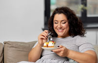 smiling young woman eating cake at home