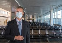 Senior adult businessman wearing a face mask against coronavirus in airport terminal