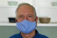 Portrait of senior caucasian man wearing face mask at home