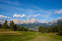 Cortina d`Ampezzo with green meadows and alpine peaks