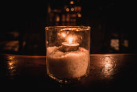 Isolated tealight inside a glass illuminating a dark scene and reflections on a wooden table and a nice bokeh background
