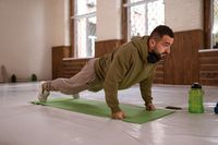 Muscular sportsman doing exercises alone in gym. Young handsome sports guy doing push ups exercise in empty gym with green bottle of water next to him all in khaki color clothes