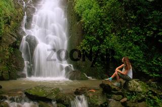 Young woman sitting at Simangande falls on Samosir island, Sumatra, Indonesia