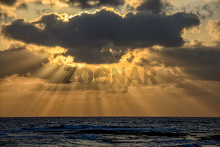Sunset with sun beams over the sea