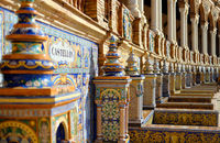 Along wall are 48 alcoves with designed on colourful azulejos painted ceramic tiles benches one for each province of Spain, close up image, Plaza de España, Seville, no people