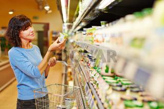 Frau kauft Joghurt im Supermarkt