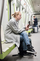 Portrait of lovely girl typing message on mobile phone in almost empty public subway train. Staying at home and social distancing recomented due to corona virus pandemic outbreak