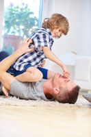Vater mit Sohn beim Toben zu Hause
