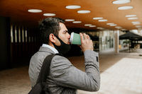 Successful young businessman walking and drinking coffee. Outdoor.
