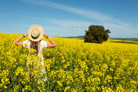 Woman in white dress in field of golden canola