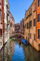 VENICE, ITALY - AUGUST 22, 2016: Tourists ride in gondola through the canal on August 22, 2016 in Venice Italy