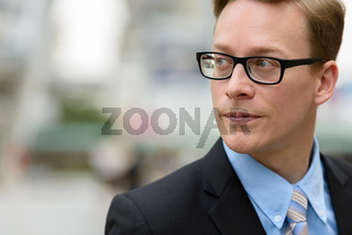 Young handsome blond businessman with eyeglasses thinking in the city outdoors
