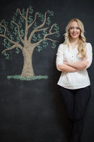 Happy blonde Business woman in front of chalk money tree drawing on blackboard.