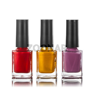different colors of nail polish in bottles isolated on white