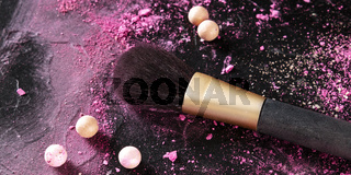 A make-up panorama with a brush with crushed cosmetics and pearls on a dark background, with a place for text