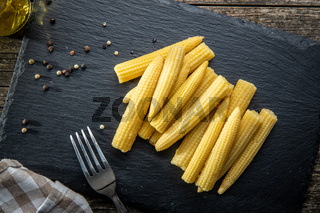 Pickled young baby corn cobs on black stone cutting board.