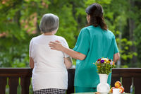 Care worker spending time with senior woman in nursing home care center