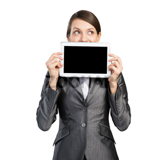 Businesswoman with tablet computer looking away