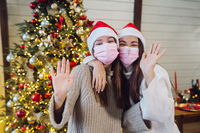 Two girls in protective masks looking at the camera and waving