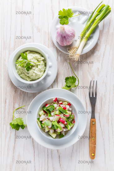 Radish salad with cucumber and onion with delicious avocado dip. Healthy food concept.
