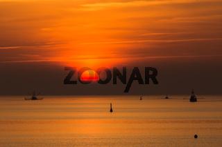 Silhouette von Fischkuttern auf der Nordsee bei Sonnenuntergang, Büsum, Deutschland