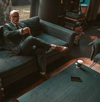 Adult respectable bald businessman looking at watches on his hand waiting for a business meeting in an business suit while sitting in dark leather sofa in the office reception. Business concept